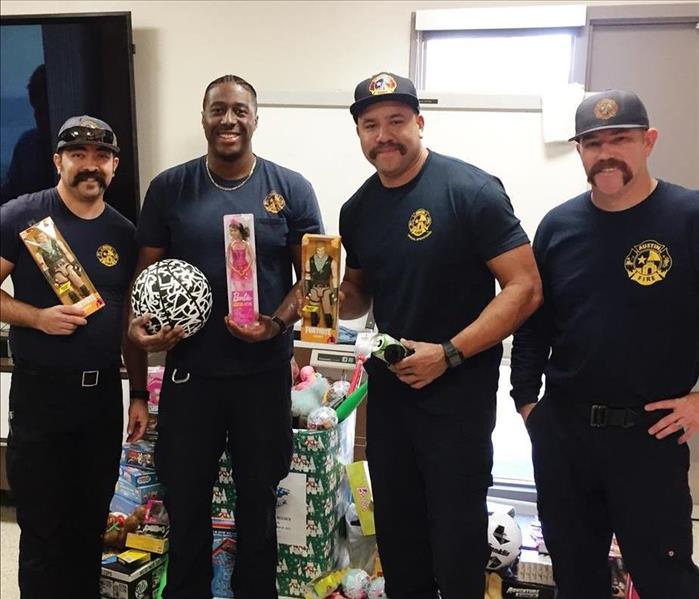 Firefighters holding toys