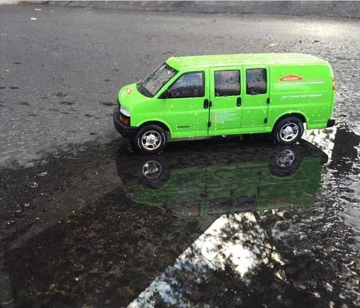 green SERVPRO van in parking lot with water standing