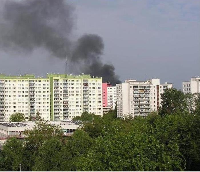 multiple high rise buildings with black smoke rising from top