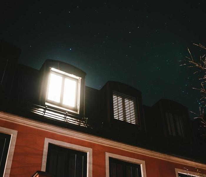 Exterior of a house at night with a single window lit